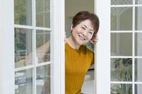 扉を開けて顔を出す笑顔の日本人のシニア女性