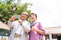 携帯電話を見る日本人シニア夫婦