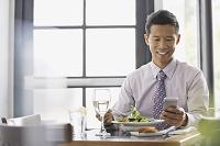 スマートフォンを操作しながら食事をするビジネスマン