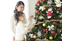 クリスマスツリーの飾りつけをする日本人親子