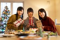 クリスマスパーティーでプレゼントを持ち微笑む日本人女性