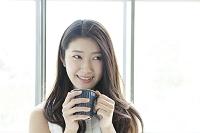 カップを持って微笑む20代日本人女性