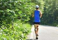 緑多い道を走るランナー