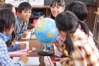 地球儀を囲んでディスカッションする日本人の小学生