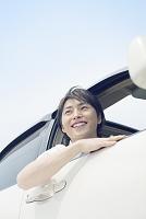 車窓から顔を出す笑顔の若い男性