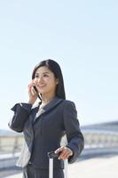 スーツケースを持ち携帯で話をするビジネスウーマン