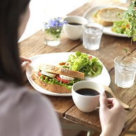 カフェでワンプレートランチを食べる女性の後姿