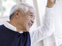 窓辺から遠くを見るシニアの日本人男性