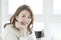 コーヒーカップを持つ笑顔のビジネス女性