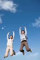 ジャンプしている笑顔のカップル