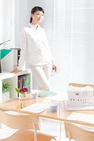 建築模型が置かれたテーブルとビジネス女性