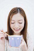 カップスープを飲む女性