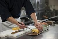 だし巻き卵を皿に盛り付ける調理師