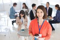 笑顔の日本人ビジネスウーマンとミーティングする人々