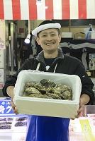 牡蠣を持って立つ鮮魚店の男性店員
