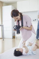 一眼レフで写真を撮る母親