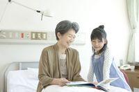 ベッドの上で孫娘と本を読む年配患者