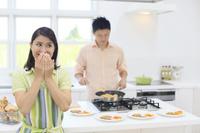 明るいキッチンで料理をする男性と笑う女性