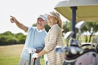 ゴルフクラブを持つシニア夫婦