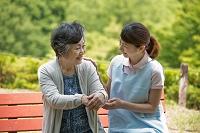 公園で話すシニア日本人女性と介護士