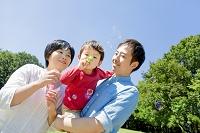 公園でシャボン玉を吹いて遊ぶ日本人親子
