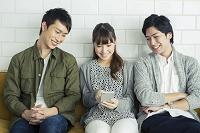一つのスマートフォンを眺める若者たち