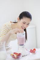 ミキサーの蓋を押さえる日本人女性