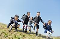 桜の咲く公園を走る新一年生