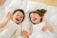ベッドで転がる男の子と女の子