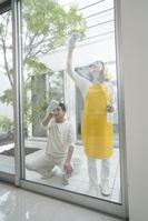 窓拭きをする中高年夫婦
