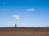 土塀の上を歩く男性と青空