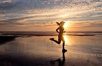海岸をジョギングする外国人女性