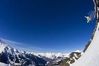 崖からジャンプするスノーボーダー