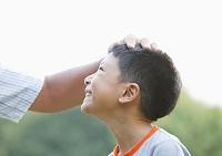 頭を撫でられる笑顔の少年