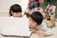 パソコンを見て笑う男の子と女の子