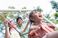 ブランコで遊ぶ女の子と夫婦