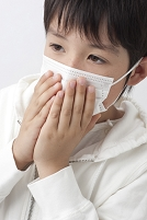 マスクに手をやり咳をする日本人の男の子