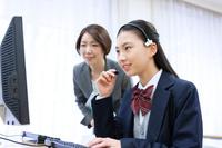 パソコンの指導をする教師と女子高校生
