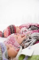 寝転んで雪を食べる子供