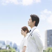 遠くを眺める医師と看護師