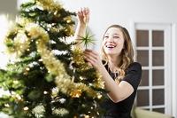 クリスマスツリーを飾り付ける女性