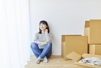 引越の荷造りをする日本人女性