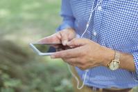 音楽を聴くスマートフォンを見る男性