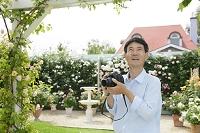 バラの写真を撮る中年日本人男性