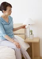 ベッドで目覚まし時計を見るシニアの女性