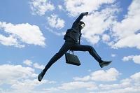 ジャンプするビジネスマンと青空