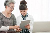 タブレットを見る祖母と孫娘