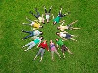 友人と円になり芝生に寝そべる若者