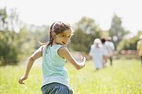 草原を走りながら後ろを振り向く女の子