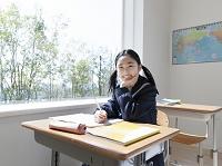 教室で頬杖をつく女子中学生